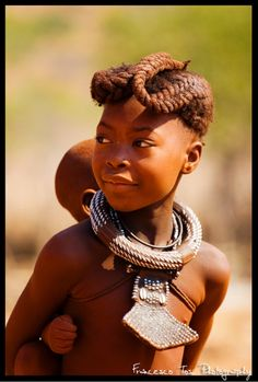 Africa | Himba girl carrying a child on her back. Epapa Falls, Namibia | ©Francesco Tosi
