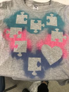 We made t-shirts at school using spray paint and wooden puzzle pieces and hearts for autism awareness month!