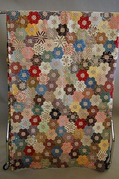An unfinished patchwork coverlet, the patches mainly 1860-70 but including some 1830s chintzes, the original paper templates retained on the reverse, 270 by 223cm, 106 by 88in
