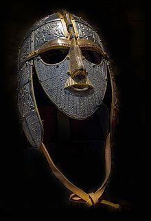 Photographie d'un casque métallique équipé de garde-joues, d'un masque facial et d'une jugulaire en cuir. La surface métallique est décorée ...