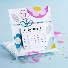 Make a monthly calendar with removable pages by punching two small holes in the top of each calendar page and attaching the stack of pages to the background with mini brads. Choose a simple design that will last through the year. Flowers cut from patterned paper create a graphic look that will stand the test of time. Display this calendar in a CD case or on a mini easel.