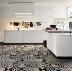 Black and white mix and match tiles provide contrast to this otherwise white kitchen.  Cle tiles offer a collection of Moroccan Handmade Encasutic TIles in black, white, and gray patterns. Photograph via Mechant Design.