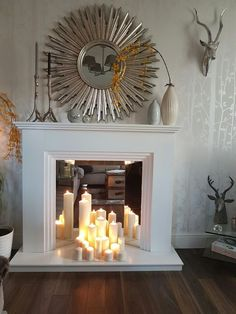 a faux white fireplace with a mirror screen and pillar candles, a sunburst mirror, vases on the mantel for decor Bookshelves In Living Room, Fireplace Bookshelves, Living Room Mirrors, Living Room With Fireplace, New Living Room, Living Room Modern, Living Room Designs, Living Room Decor, Office Bookshelves