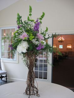 Lovely tall purple and green centerpiece with woven branches | pod shop flowers wedding designs |  #wedding #centerpiece #flowers #arrangement
