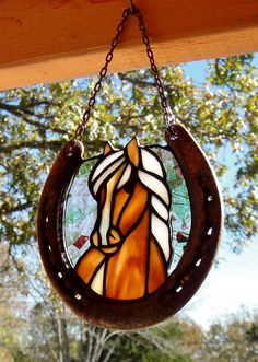Brown horse with white blaze stained glass suncatcher in recycled horseshoe frame. Created by Janice Finn Culp.