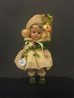 """VOGUE HARD PLASTIC GINNY FROM THE DEBUTANTE SERIES. STRUNG BODY, SOFT YELLOW BLONDE DYNEL SIDE-PART WIG, BLUE SLEEP EYES, PAINTED LASHES, WEARS TAGGED """"VOGUE"""" YELLOW ORGANDY DRESS WITH GREEN VELVET TOP AND FLORAL ACCENT, MATCHING PANTY AND HAT, GREEN VELVETEEN SHOES WITH YELLOW SOCKS. RETAINS ROUND SILVER HANG TAG."""