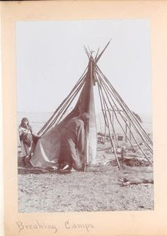 Breaking camps, 2 women taking down a tipi. Hard workers