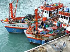 Colourful photo of a couple of fishing boats and the fisherman.