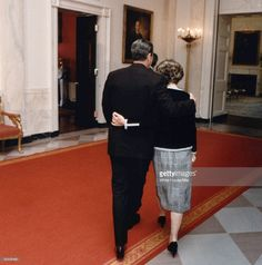 President Ronald Reagan and wife, First Lady Nancy Reagan, walking towards State dining room in the White House w. arms around each other.