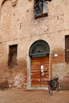 Bike parked in front of ancient building in rinascimental Ferrara, Italy