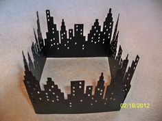 Cricut Cityscape scene cut on glitter paper and pieced together for a table centerpiece for a Superhero Baby Shower.