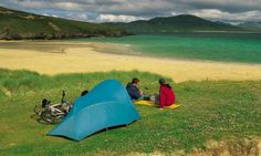 Two cyclists sitting outside their tent while camping on Horgabost beach on the Isle of Harris