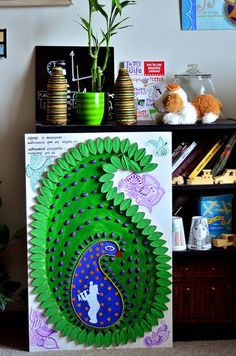the peacock paisley artwork is created on a poster board using toilet paper rolls, pistacho shells, acrylics and beads.