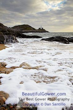 """Bracelet Bay and Mumbles Lighthouse by Dan Santillo. """"I took my family here on what was a bitterly cold January morning. Whilst my wife was playing with the children, misjudging the waves and getting wet feet, I took a few photos of the foam created as the waves swept rolled up the beach."""""""