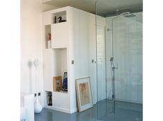 À côté la douche, un espace clos succède à de grands rangements qui occupent le mur du fond. À l'intérieur, se trouvent les toilettes et le lave-linge, l'accès s'effectue par une porte coulissante. Les niches orientées vers l'intérieur de la pièce dessinent des formes géométriques où les parties pleines alternent avec les creuses, juste reliées aux angles.