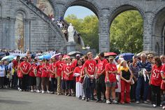 young adults from #rome participate in the eucharistic procession at #lourdes