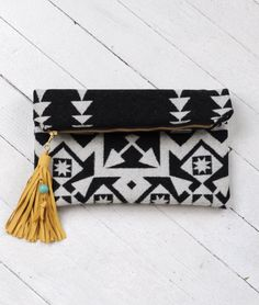 "Nighthawk ClutchDesigner: s e a e c h o$68.00 Striking jacquard clutch crafted from virgin Pendleton wool made exclusively for Summerland by s e a e c h o. Features a thick leather tassel with turquoise bead detail and sturdy canvas lining. Measures 14"" x 12"" and 14"" x 9"" when folded. The perfect size to hold all the essentials with easy transition from day to night."