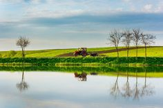 A tractor passing near a lake from Bosanci village, Suceava County, ROMANIA, this spring