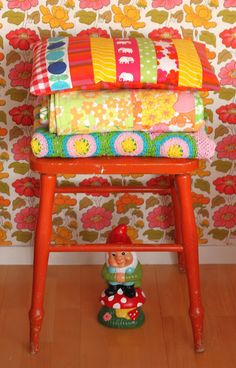 I love these vintage bedding and pillows on the red stool! And also fabulous wallpaper!