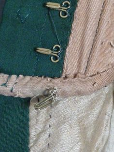 "eBay| Mid-1800s : All hand-made. Outer fabric wool (green) wt velvet (black) trim. Inner lining muslin (beige). Built-in corset. Metal strips are sewn into jacket's fabric. Buttons on outside are decorative. Closes wt hook & eyes on inside. It also has a 'cumberbund' that attaches at the waist at the very bottom of the jacket.  Neck, side to side 4 1/2"" Shoulder seam to shoulder seam 18"" Bust armpit to armpit 14"" Waist 11"" Nape of neck to bottom 21"" Sleeve length from seam to bottom 19"""