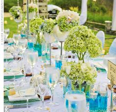 In addition to the custom-made seashell vases, tables were decorated with tall centerpieces filled with hydrangeas, orchids, and peonies, and adorned with hanging crystal accents.