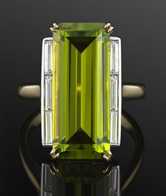 Peridot and Diamond Cocktail Ring, circa 1970s. A long emeral cut peridot weighing approx 4 carats is accented to either side with a row baguette diamonds in an 18 karat yellow gold mounting