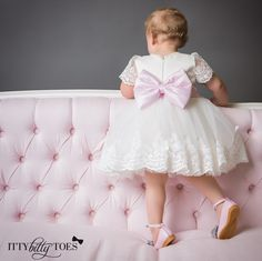 A lovely white and lace dress with a pink stuffed bow - perfect for any special occasion! Offered by Itty Bitty Toes!