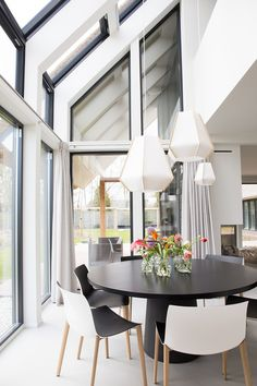 Dark round dining table, white and light wood chairs (no black), 3 suspended white light fixtures.  Femkeido Interior Design