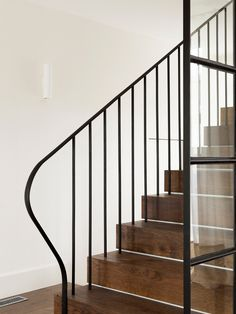 Dark oak treads and a classic steel balustrade provide a contrast against the white walls.