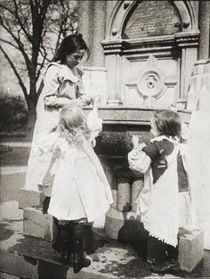 Broadwater Victoria fountain, Worthing. Three girls looking into the fountain and playing with the water. Wearing traditional Victorian dress, pinafores and lace up boots. c1880s
