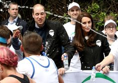 Kate Middleton Photos Photos - A runner squirts water towards Britain's Prince William, Duke of Cambridge and Britain's Catherine, Duchess of Cambridge as they hand out water to runners during the 2017 London Marathon in London on April 23, 2017. / AFP PHOTO / POOL / Chris Jackson - The Duke & Duchess of Cambridge and Prince Harry Attend the Virgin Money London Marathon