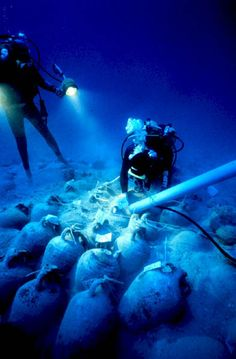 Bozburun Byzantine shipwreck: Built - 874 AD, Sunk - c 880 AD. Under the jumbled amphoras was a layer of jars still stacked in orderly rows, left behind nearly 1,200 years ago. Here a diver cleans out the spaces between amphoras. Small finds are often found wedged down in these spaces.