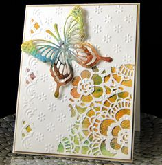 Designed and Created by Peggy Dollar This card was finished up with tiny half pearls in the middle of each embossed flower. I failed to get a photo of it before I mailed it off! Also the butterfly and underlying water colored piece has considerable shine which I also did not capture. The EF is a cut and emboss Marianne Design folder. The lace cut is from Tim Holtz mixed media dies.The last framing piece is a satin metallic gold.