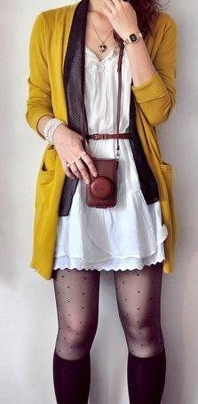 Layers! Yellow cardigan with a neutral layer inside, a white dress, brown leather belt, brown leather purse, black spotted stockings