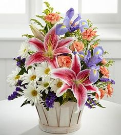 Mother's Day Gift Idea - The FTD Wondrous Nature Bouquet is bountifully bedecked with a dazzling display of color and beauty. Stargazer lilies stretch their fuchsia petals out amongst an arrangement of blue iris, white traditional daisies, orange mini carnations, purple statice and yellow solidago in a round whitewash handled basket.