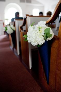 Love the bright cobalt blue cones against the crisp white flowers in these pew flower arrangements