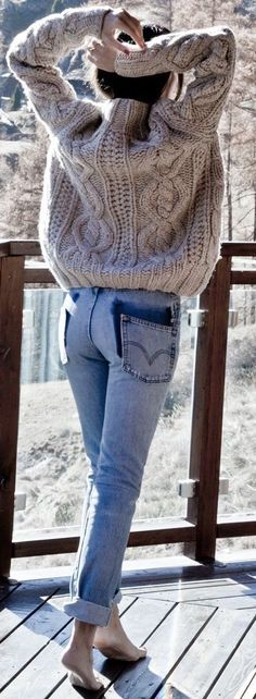 Beige cable knit sweater with blue jeans.