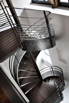 DH83 - SPIR'DÉCO® Caisson. Escalier intérieur métal et bois en colimaçon sur 2 niveaux pour une décoration design et contemporaine type loft. Limon formant ruban en extérieur des marches soulignant les courbes de l'escalier hélicoïdal. Rampe et garde-corps de mezzanine graphiques et contemporains. Finition : Acier brut patiné pour une finition naturelle et intemporelle. - © Photo : Ludovic DI ORIO
