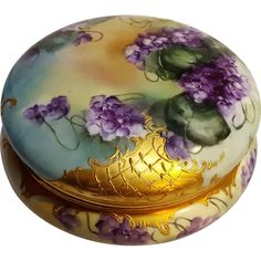 Tressemann  Vogt TV Limoges porcelain powder jewel box with hand painted violets and heavily applied gold gilt lattice.  The jar measures 8 across and