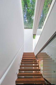 Sob a claraboia, a escada tem sua estrutura metálica embutida na parede. Na lateral, o fechamento de vidro vai do piso ao teto.