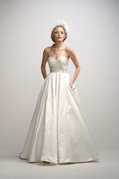 Ivory soft silk duchess satin sweetheart neck ball gown with pleated bodice, natural waist accented with a fresh water pearl applique, full shirred skirt with pockets and a chapel train.