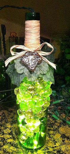 Inspiration...Looks like this is made w/ a green wine bottle w/ green flat glass marbles (the kind you usually find for fish tanks) glued to it, attached fake Ivy leaves and an Ivy trinket, raffia wrapped around the top and tied in a bow, and Christmas lights put in it