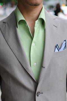 ベージュのジャケットにグリーンのニットシャツ=ビズポロ