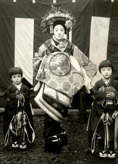 """This postcard shows a Tayuu (Japanese Courtesan) and two Kamuro (Child Attendants) standing in front of a Kōhaku-maku (red and white curtain). A Kōhaku-maku is a type of decorative fabric panel used on various occasions in Japan, such as outdoor tea ceremonies.""  1920's, Japan. °"