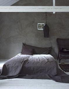Déco minimaliste pour une chambre taupe, une teinte sombre relevée par la couleur du linge de lit parme et chocolat.