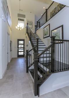 Gehan Homes Stairway - Black Hardwood Tread, White Risers, L-Shaped Staircase, Open Staircase, Light Gray Tiled Flooring