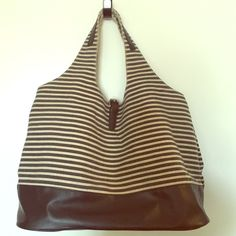 """NWOT Striped Tote w black leather bottom JUMBO! You can fit everything in this bag. Color is a tan canvas and black stripe with faux leather bottom. Silver buckle closure and drawstring interior to keep your contents safe. 16.5""""w x 8.5""""d x 12""""h + 10"""" handle drop. Don't remember ever using this. Open to offers and bundle discounts! Bags Totes"""