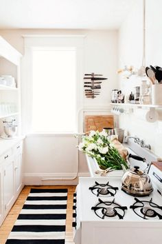 white kitchen with striped runner and magnetic knife rack and tea kettle . Runner makes galley kitchen feel bigger while hiding flooring