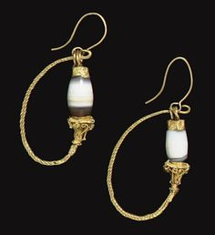 A PAIR OF GREEK GOLD AND BANDED AGATE EARRINGS   HELLENISTIC PERIOD, CIRCA 1ST CENTURY B.C.   Each formed from a hoop of spirally-twisted wire terminating in a cluster of granulation surmounted by a capital of openwork filigree beaded wires and granulation around a hollow tube, flaring to a square cornice, with granules at the corners, threaded through a barrel-shaped banded agate, with a plain sheet cap, the wire spiral-looped at the end; surmounted by modern gold earwires