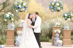 Twilight blue and blush pink wedding. Periwinkle and white hydrangeas, white and blush pink roses. Damask blue and white vases. Dusty blue wedding dress and the groom in a white dinner jacket.